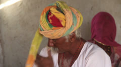 India Rajasthan Manvar metal worker winds turban and veiled woman  Stock Footage