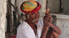 India Rajasthan Manvar metal worker with turban blows smoke  Stock Footage