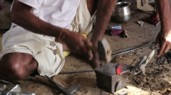 India Rajasthan Manvar metal worker pounds red hot blade Stock Footage