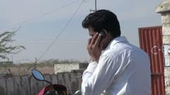 India Rajasthan Jaisalmer station man on scooter talks on phone  Stock Footage