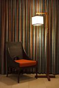 Rattan chair with warm white lamp Stock Photos