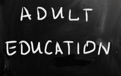 """adult education"" handwritten with white chalk on a blackboard Stock Illustration"