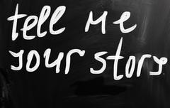 "Stock Illustration of ""tell me your story"" handwritten with white chalk on a blackboard"