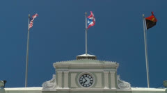 Flags fly atop government building Stock Footage