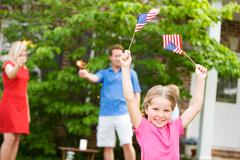 Stock Photo of summer: girl in front yard with american flags