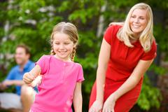 summer: mom supervises daughter with sparkler - stock photo