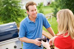 Summer: man standing with woman on deck with wine Stock Photos
