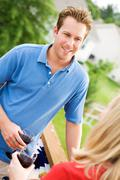 summer: couple standing on deck with wine - stock photo
