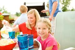 summer: family having dinner on deck - stock photo