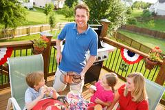 summer: dad serves up hamburgers and hot dogs - stock photo