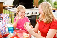 Summer: girl stealing chip from mother Stock Photos