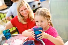 summer: girl drinking lemonade at table - stock photo