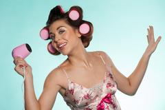 woman in haircurlers with hairdryer - stock photo