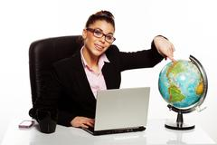 smiling manageress pointing to a globe - stock photo