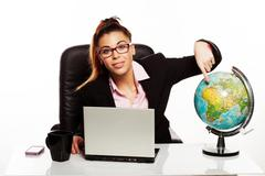 Stock Photo of businesswoman pointing to a world globe