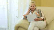 Stock Video Footage of Mature woman with financial document on the phone