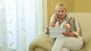 Stock Video Footage of Mature woman doing paperwork on the phone at home