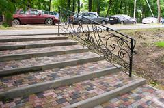 Staircase with steps of paving slabs with metal railing Stock Photos