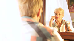 Senior woman looking into mirror - stock footage