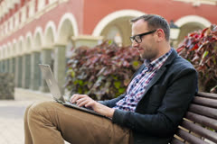 Young man in tourist resort working with laptop computer, steadicam shot Stock Footage