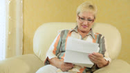 Stock Video Footage of Cheerful senior woman reading some financial paper