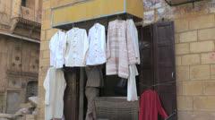 India Rajasthan Jaisalmer shirts hung by shop door Stock Footage