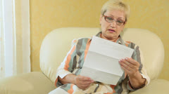 Senior woman looking at a bank statement - stock footage