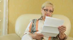 Mature woman looking at a bank statement - stock footage