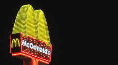 McDonalds sign by night symbol advertising neon light illuminated ad dark Stock Footage