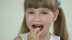 Girl eating strawberries and looking at camera with smile Stock Footage