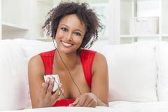 African american girl listening to mp3 player headphones Stock Photos