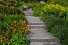 Flower bed with plants and road to stairs Stock Photos