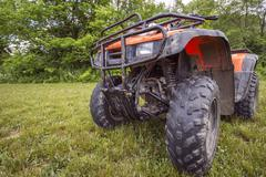 Muddy Four Wheeler sitting in Grass Stock Photos
