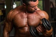 Stock Photo of bodybuilder doing heavy weight exercise for biceps with dumbbell