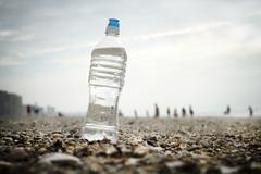Stock Photo of Water Bottle On Seashells At The Beach