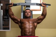 Male bodybuilder doing heavy weight exercise for upper chest Stock Photos