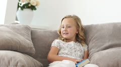 Girl reading a book on sofa and  smiling Stock Footage