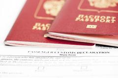 Two passports are on the passenger custom declaration Stock Photos