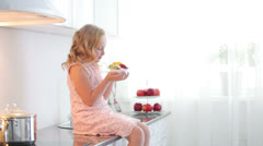 Little girl sitting on table and holding plate of fruit yoghurt Stock Footage