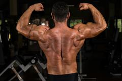 muscular bodybuilder showing his back double biceps - stock photo