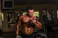 bodybuilder doing heavy weight exercise for biceps with dumbbell - stock photo