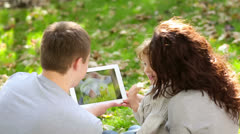 family using tablet pc in autumn park - stock footage