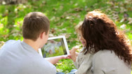 Family using tablet pc in autumn park Stock Footage