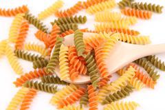 A pasta eliche tricolori and a wood spoon. Stock Photos