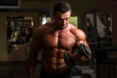 Bodybuilder doing heavy weight exercise for biceps with dumbbell Stock Photos