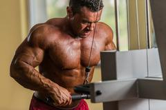 Bodybuilder doing heavy weight exercise for triceps with cable Stock Photos