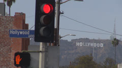 Hollywood sign, Hollywood Boulevard sign with traffic light by day, palm tree Stock Footage
