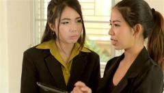 Two asian office workers explaining work with a tablet computer Stock Footage