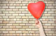 Stock Photo of brick wall and hand with balloon