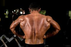 muscular bodybuilder showing back lat spread - stock photo